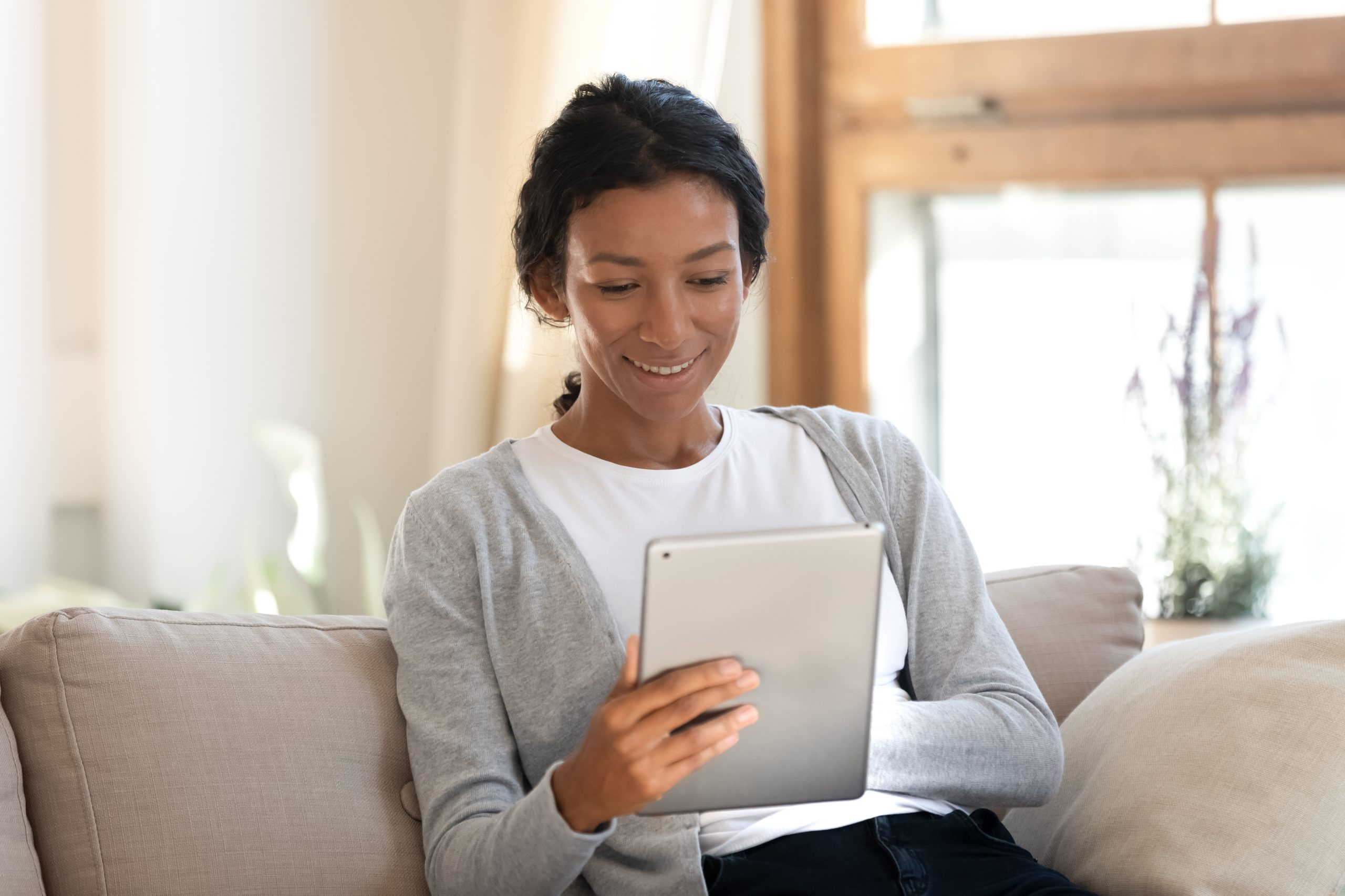Smiling biracial young female sit relax on sofa at home browsing wireless Internet on tablet, happy African American millennial woman rest on couch in living room watch video or surfing on pad gadget